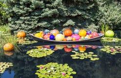 Boules en verre colorées lumineuses dans le bateau Photo stock