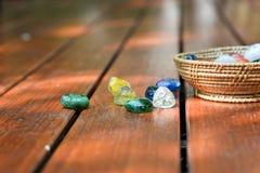 Boules en verre dans le seau sur le plancher en bois Photographie stock