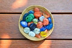Boules en verre dans le seau sur le plancher en bois Image libre de droits