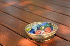 Boules en verre dans le seau sur le plancher en bois Photos libres de droits