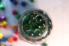 Boules en verre dans un pot en verre avec un fond brouillé Photo stock