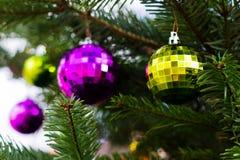 Boules en verre violettes et vertes sur l'arbre de Noël Photographie stock libre de droits