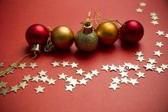 Boules et étoiles de Noël sur le fond rouge Photographie stock