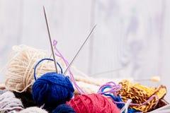 Boules et aiguilles colorées de laine dans le panier en bois Image libre de droits
