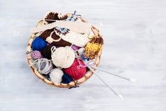 Boules et aiguilles colorées de laine dans le panier en bois Photo stock