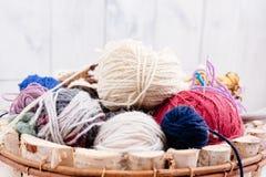Boules et aiguilles colorées de laine dans le panier en bois Photo libre de droits