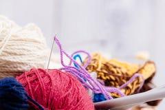 Boules et aiguilles colorées de laine dans le panier en bois Photos stock