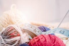Boules et aiguilles colorées de laine dans le panier en bois Photographie stock libre de droits
