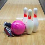 Boules et chaussures de bowling avec des quilles Photos stock