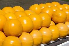Boules jaunes de fromage de pile sur l'étagère photographie stock
