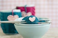 Boules lumineuses de fil dans des plats bleus et de coeur fait de feutre Images libres de droits