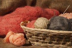Boules multicolores de fil dans un panier de paille sur renvoyer Image stock