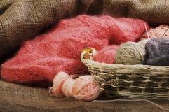Boules multicolores de fil dans un panier de paille sur renvoyer Images stock