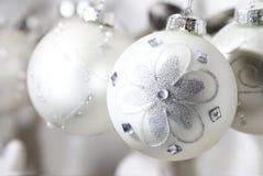 Boules nacrées de Noël avec des conceptions des fleurs brillantes lumineuses Photographie stock