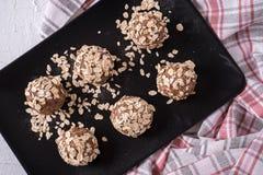 Boules organiques saines d'énergie faites avec des dates, flocons d'avoine, canneberges sèches, noix de pécan, dans le plat noir  images stock