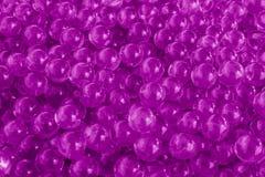 Boules pourpres de gel de l'eau avec le bokeh Gel de polymère Silicagel Boules d'hydrogel pourpre Boule liquide en cristal avec l photographie stock libre de droits