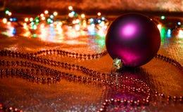 Boules pourpres de Noël sur les lumières de fond Images libres de droits