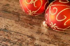 Boules rouges de Noël avec la décoration d'or sur la table en bois photographie stock