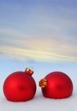 Boules rouges de Noël dans la neige Photo stock
