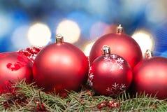 Boules rouges de Noël sur le fond bleu brouillé Photographie stock libre de droits