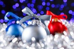 Boules rouges, grises et bleues de Noël, lumières pourpres brouillées au fond Photographie stock