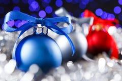 Boules rouges, grises et bleues de Noël, lumières pourpres brouillées au fond Image stock