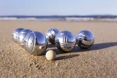 Boules set. A Boule set of six boules and a cochonnet on a sandy beach Stock Photo
