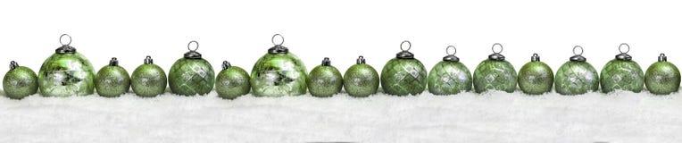 Boules vertes de Noël dans la neige Images stock