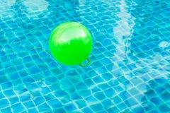 Boules vertes flottant sur l'eau bleue dans la piscine images libres de droits