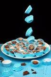Boules volantes de panier et de chocolat de papier bleu de plat sur la table en bois bleue, sur le noir Photo libre de droits