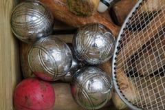 Boulesbollar och krocketklubbor och tennisracket i en ask som beskådas från över fotografering för bildbyråer