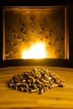 Boulettes de biomasse illuminées par la flamme de la chaufferette Photos libres de droits