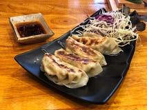 Boulettes de Gyoza en beaux plat et sauce de soja noirs sur la table en bois images stock