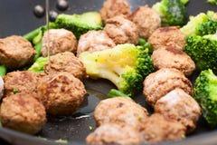 Boulettes de viande, brocoli et épinards faits sauter à feu vif Photos libres de droits