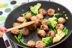 Boulettes de viande, brocoli et épinards faits sauter à feu vif Image libre de droits