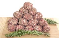 Boulettes de viande crues sur la planche à découper Images libres de droits