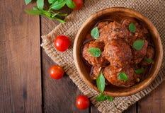 Boulettes de viande en sauce tomate douce et aigre et basilic dans une cuvette en bois photo stock