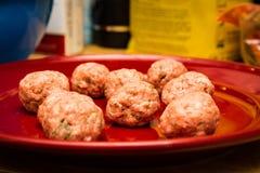 Boulettes de viande italiennes crues de plat rouge photographie stock