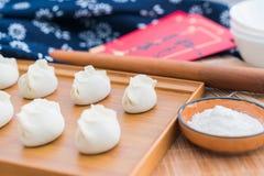Boulettes, farine, bâtons de roulement, enveloppes rouges sur la table en bois image stock