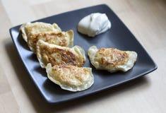 Boulettes frites et x28 ; pierogi& appelé x29 ; avec la crème sure Photos libres de droits