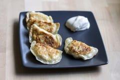 Boulettes frites et x28 ; pierogi& appelé x29 ; avec la crème sure Photographie stock libre de droits