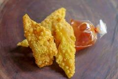 Boulettes frites, nourriture chinoise avec de la sauce dans le sachet en plastique sur la table en bois photo libre de droits