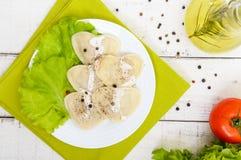Boulettes italiennes de ravioli sous forme de coeur d'un plat sur le fond en bois blanc Image stock