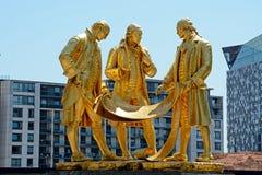 Boulton, Watt and Murdoch statue, Birmingham. View of the golden Boulton, Watt and Murdoch statue in Centenary Square, Birmingham, England, UK, Western Europe Stock Image