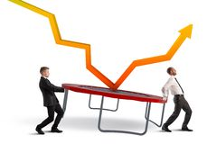 Bounce the crisis. Businessmen bounce an arrow on a trampoline Royalty Free Stock Image