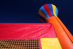 Bounce house with dark sky. Looking up at a bounce house or castle at the dark blue sky.  Child's toy is red, orange, yellow, and blue. Very popular at children' Stock Photo