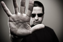 Bouncer blocking entrance. A stock photo of a man in sunglasses blocking entrance by holding up his hand. The image is low key and desaturated and has a vignette Stock Images