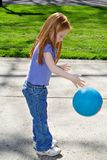 Bouncing Ball. Small red-haired girl bouncing a blue ball in her driveway Royalty Free Stock Photo