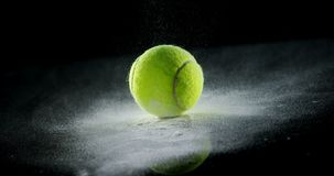 Bouncing ball with powder on black background. Close-up of bouncing ball with powder on black background stock footage