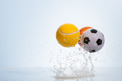 Bouncing balls. Three sport bouncing balls on water surface royalty free stock image